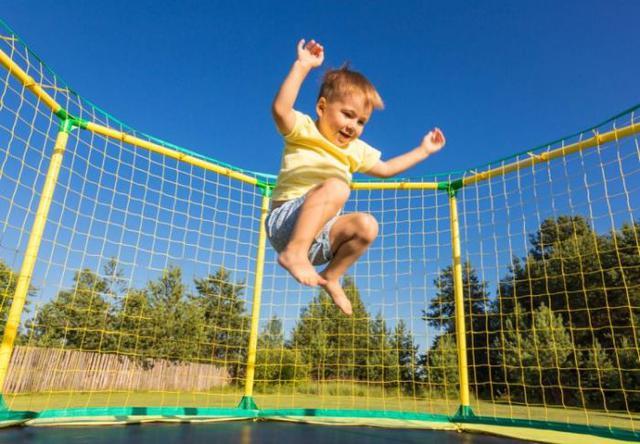 chłopiec bawiący się na trampolinie