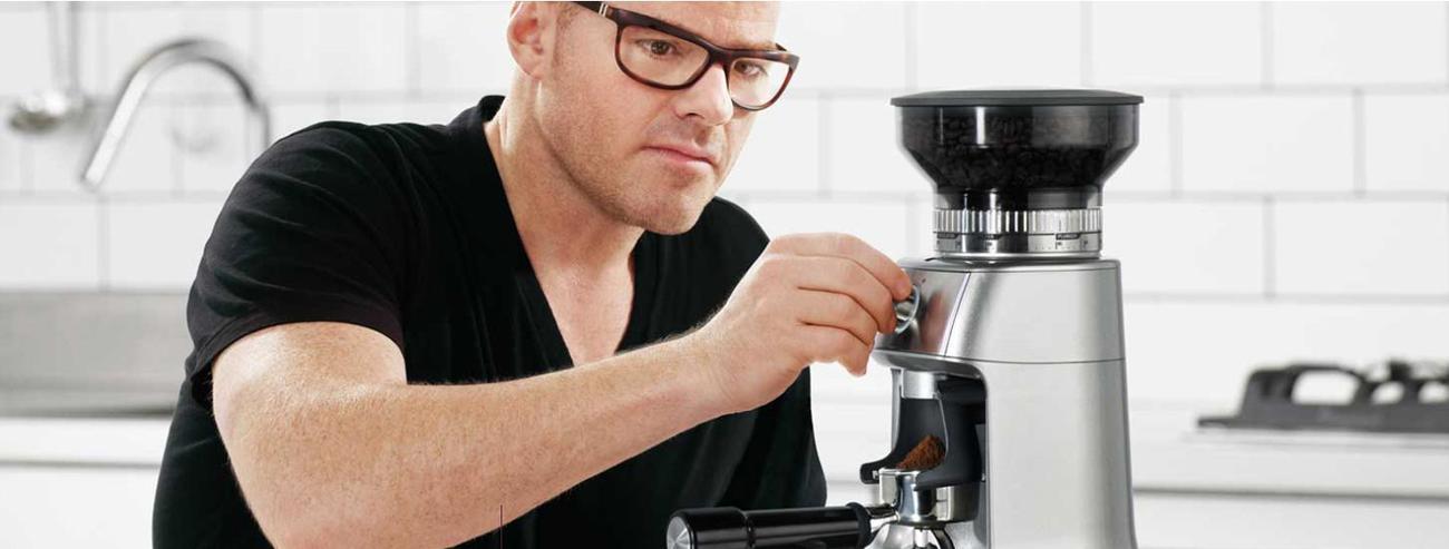 obsługa elektrycznego młynka do kawy przez mężczyznę