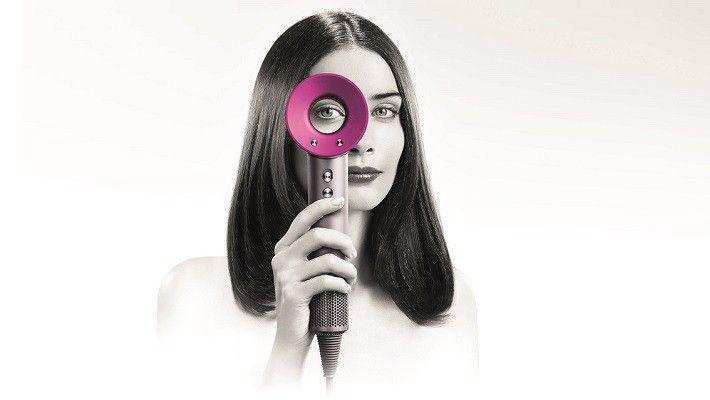 trzymanie w ręku innowacyjnej suszarki do włosów marki Dyson