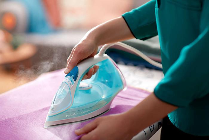 prasowanie tkaniny niebieskim żelazkiem Philips