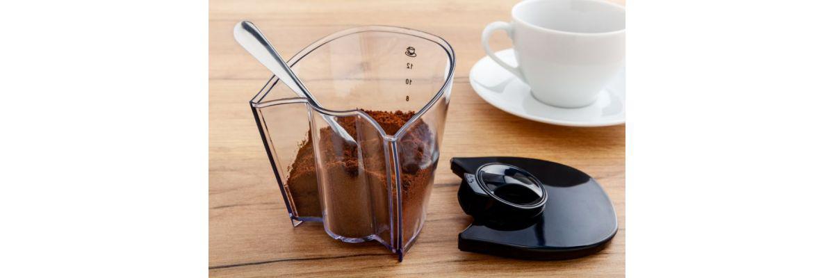 zmielona kawa w pojemniku obok białej filiżanki