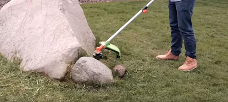 Kosa spalinowa kosząca przy kamieniu