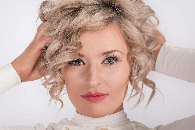 kobieta z krótkimi kręconymi blond włosami