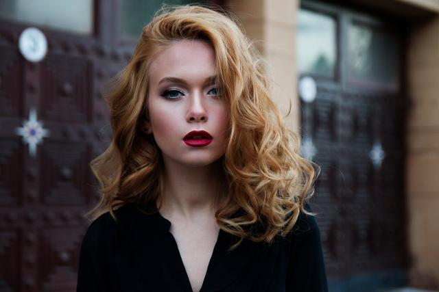 kobieta z kręconymi  półdługimi włosami