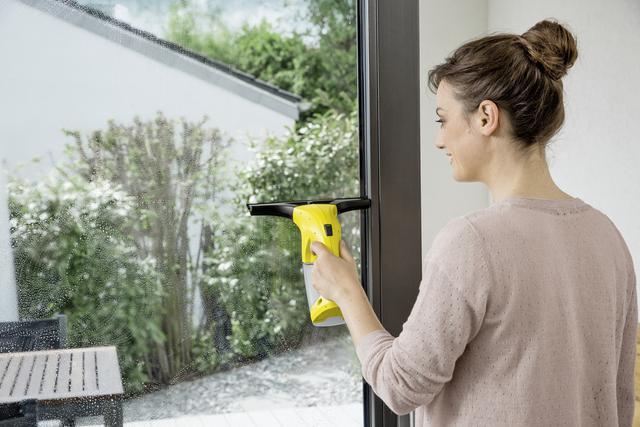 kobieta, która myje szybę myjką marki Karcher