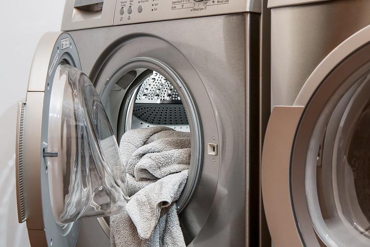 otwarte drzwiczki i ręcznik w srebrnej pralce