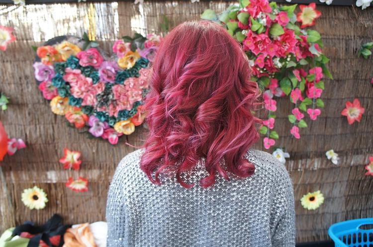 kobieta z różowymi pokręconymi włosami