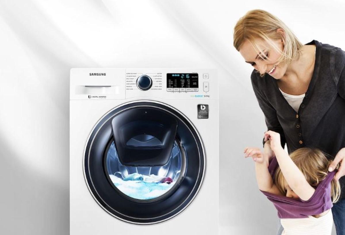 Kobieta pomaga zdjąć dziecku sweter przy pralce Samsung