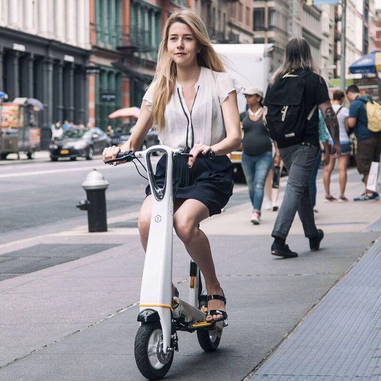 kobieta jeżdząca na elektrycznej hulajnodze z siedziskiem